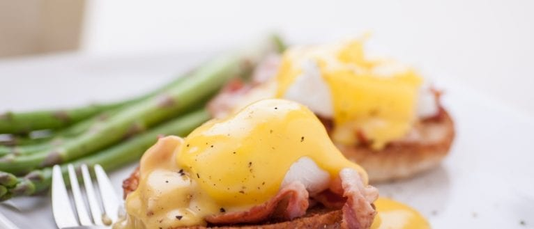 Hollandaise sauce over poached eggs, bacon and fresh bread