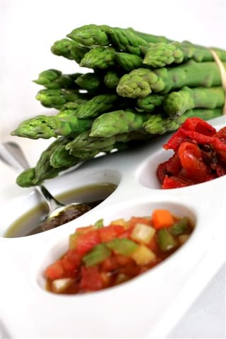 Green asparagus spears with oven-dried tomatoes and spicy root vegetable and black olive dressing
